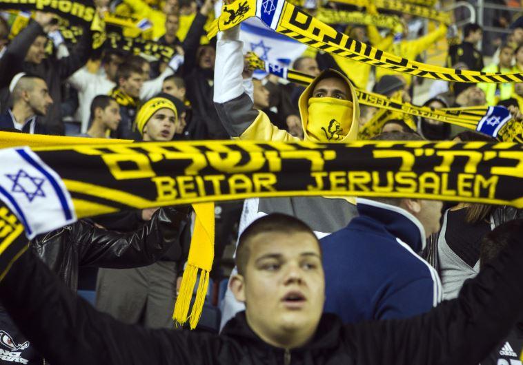 Fans of Beitar Jerusalem shout slogans during a match against Bnei Sakhnin