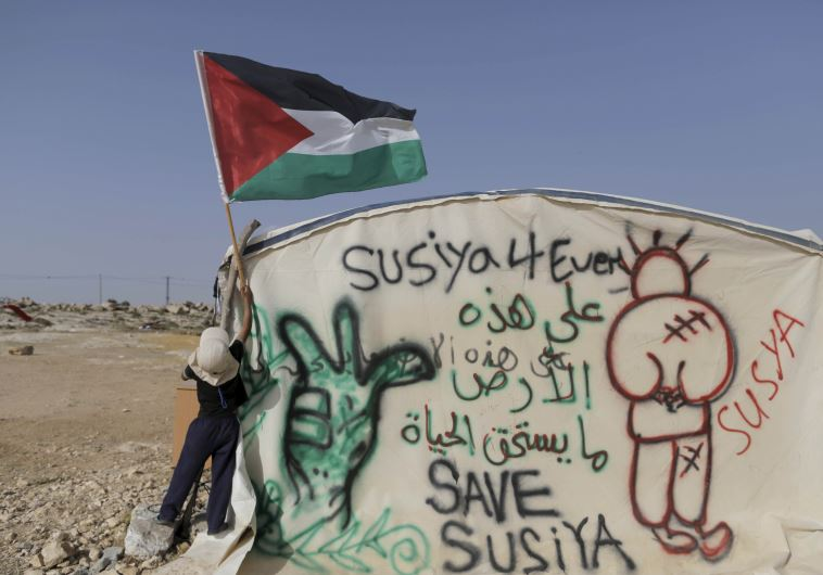 A Palestinian boy places a Palestinian flag on a tent in the West Bank village of Sussiya