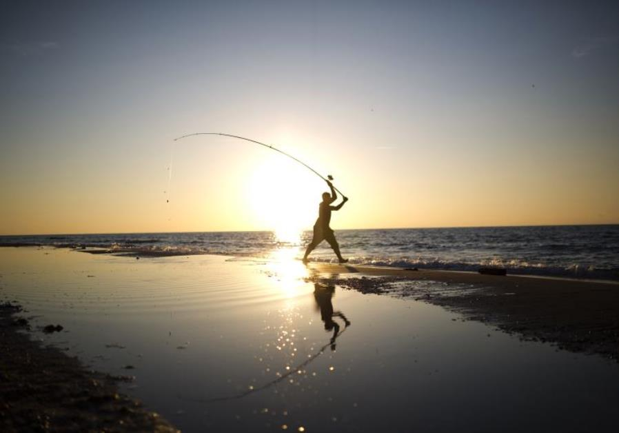 A man casts his fishing line in the Mediterranean Sea on Zikim beach, near Ashkelon