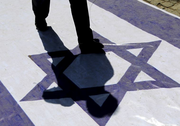 A demonstrator steps on an Israeli flag during a rally marking al-Quds (Jerusalem) Day in Tehran