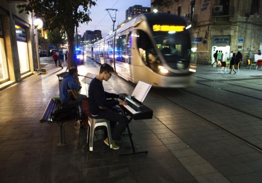 Israeli teens play music as a light rail tram passes by in Jerusalem