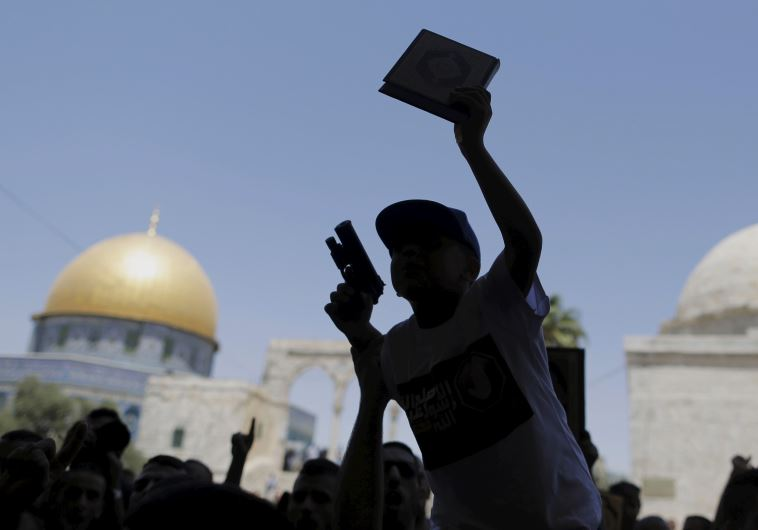 A Palestinian youth is silhouetted as he holds a toy gun and a Koran during a protest