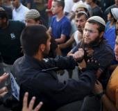 Jewish settlers (R) scuffle with Israeli police officers near buildings slated for demolition