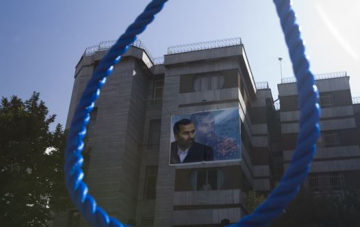 A picture of a murdered Iranian judge is seen through a noose before the hanging of his killers