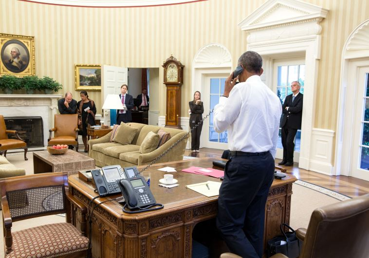 President Barack Obama talks on the phone in the Oval Office with Secretary of State John Kerry