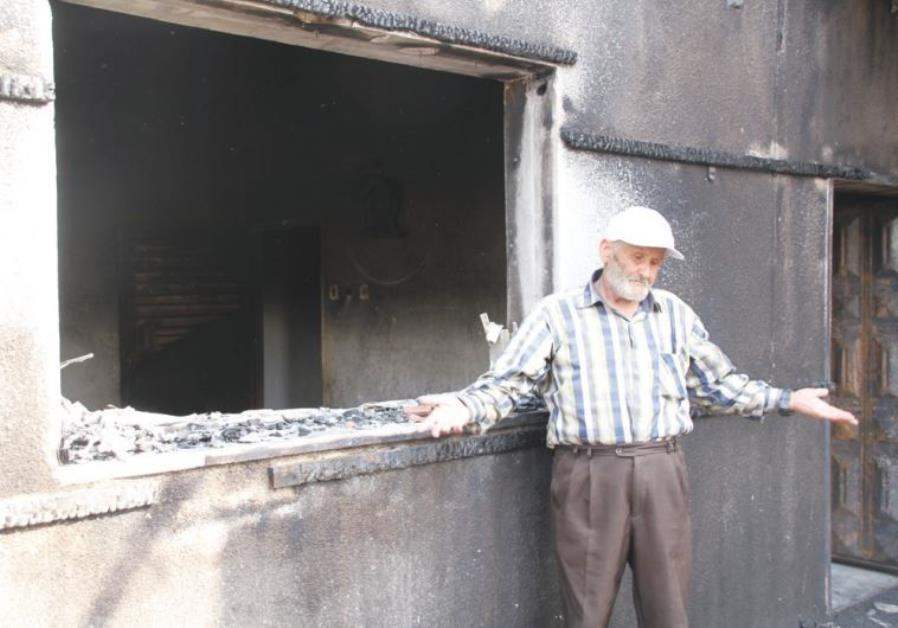 RASHID DAWABSHA stands outside his son Mamoun's torched home in the Arab village Duma on Sunday