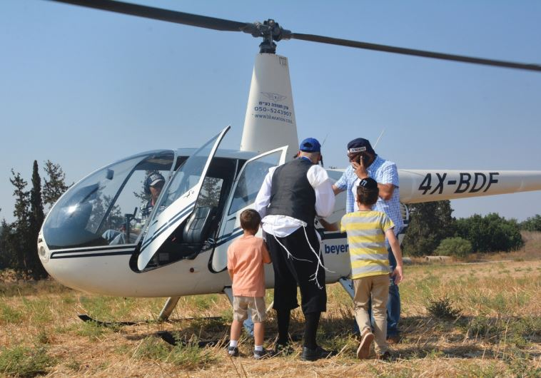 MOTTI FRIED (center) helps children from his organization Saad V'Marpe get into a helicopter for a r