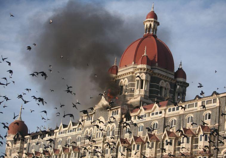 Pigeons fly near the burning Taj Mahal hotel
