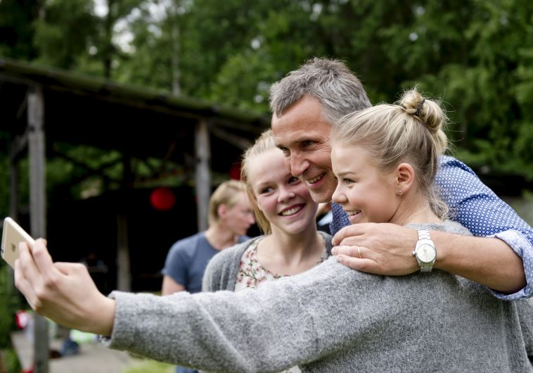 "NATO Secretary-General Jens Stoltenberg (C) takes a ""wefie"" together with two girls"