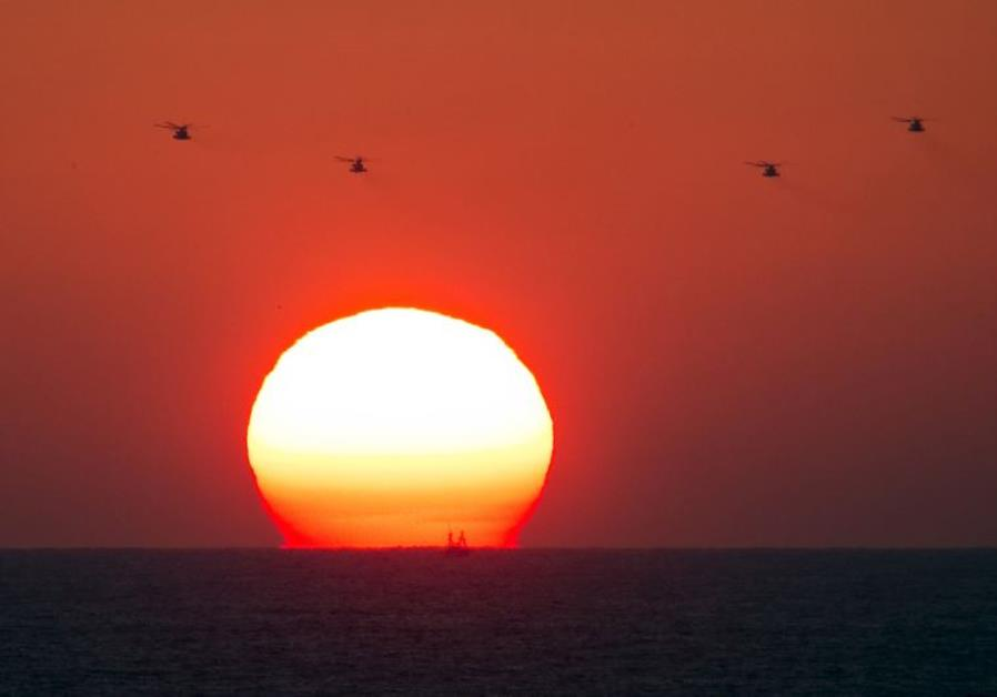 Four military helicopters fly over the Mediterranean sea opposite the port of Ashdod