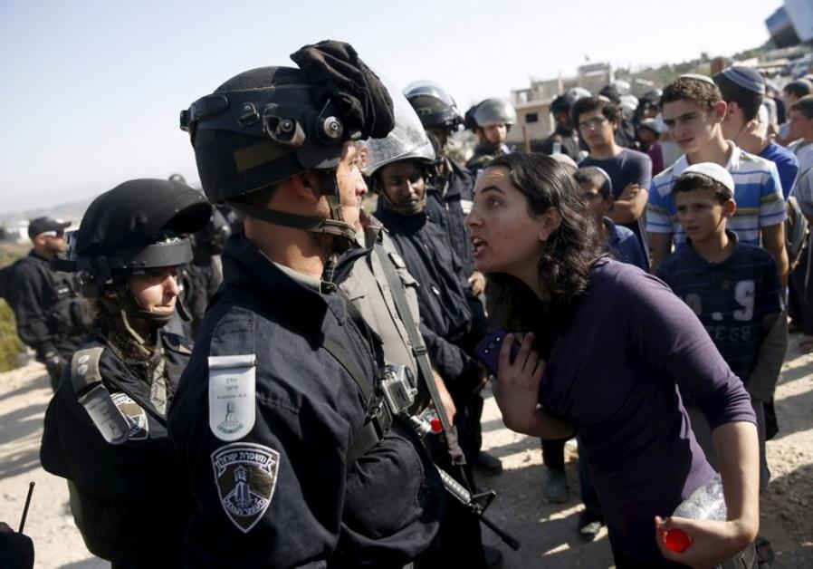 A young Jewish settler (R) speaks with an Israeli police officer