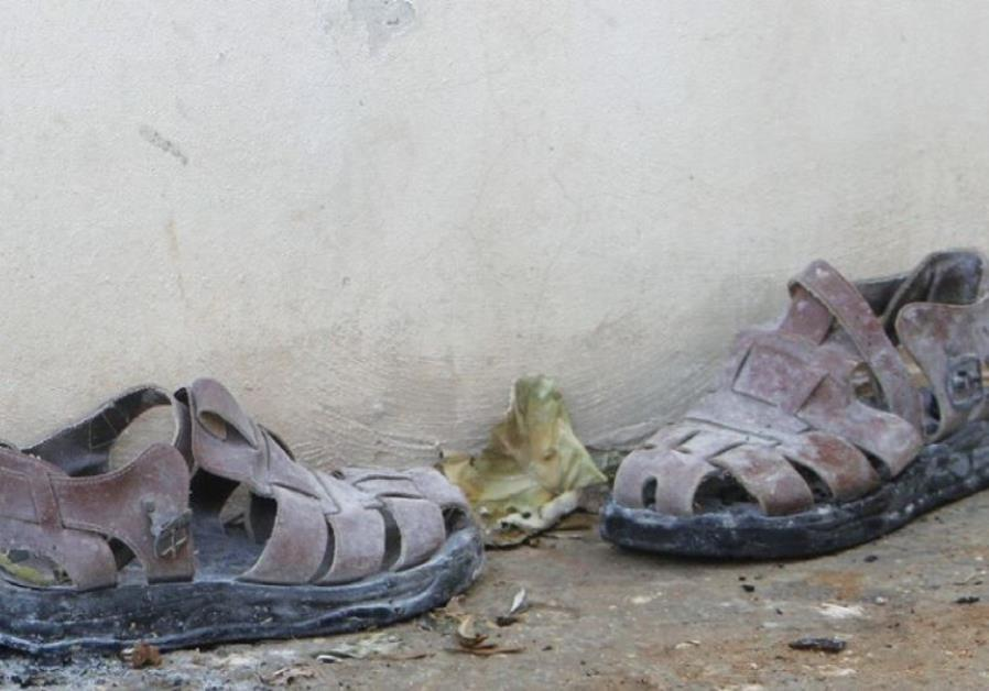 A PAIR of slippers is seen outside a house that had been torched in a suspected attack by Jewish ext