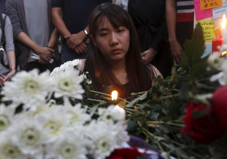 A woman lights a candle at the Erawan shrine, the site of Monday's deadly blast, in central Bangkok
