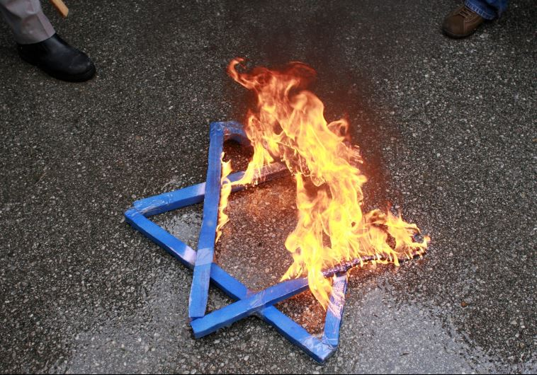 A Star of David burns in flames during a protest against Israeli attacks on Gaza
