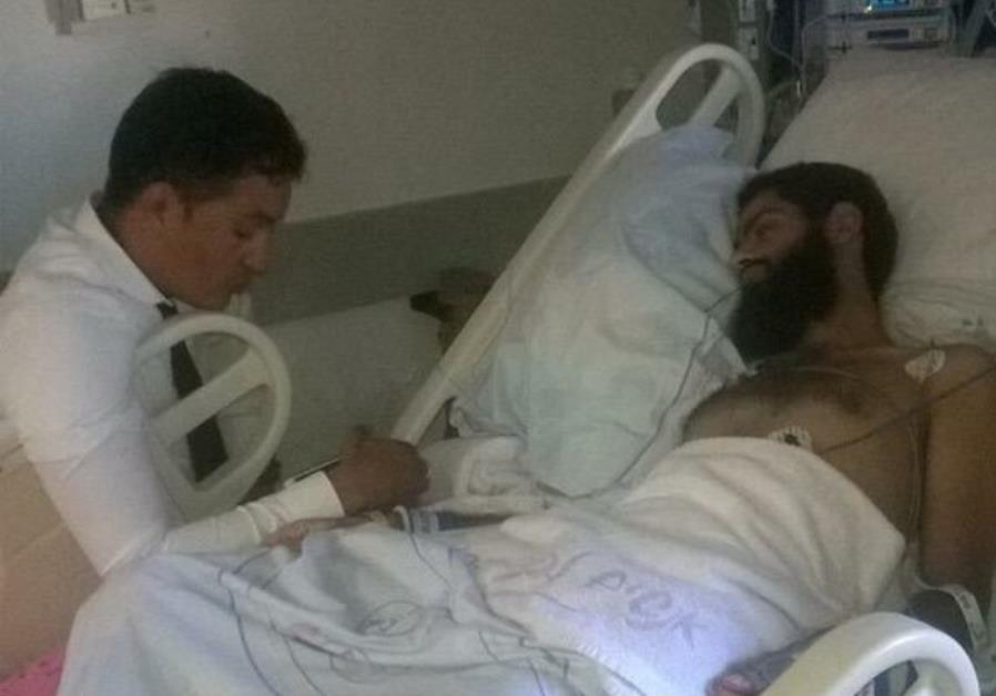 Muhammad Allan, with his lawyer, recovering in hospital