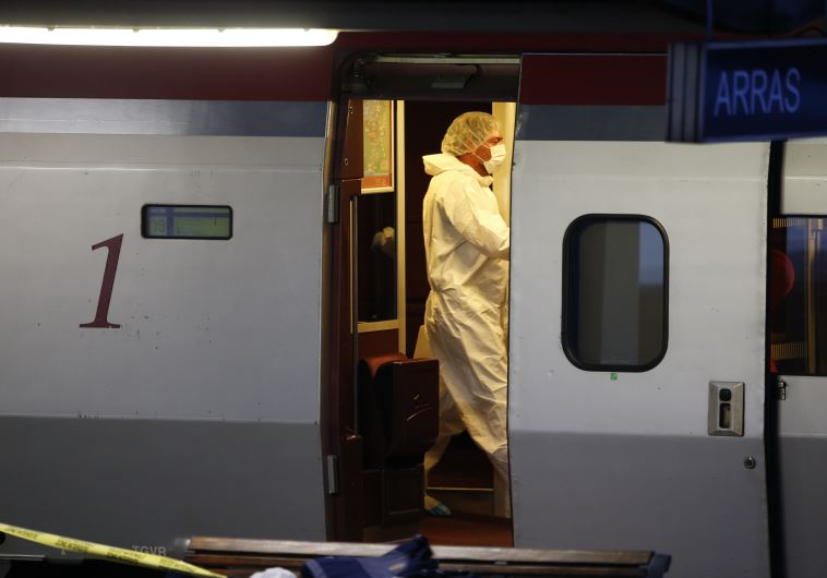 French investigating police in protective clothing collect clues inside the Thalys high-speed train