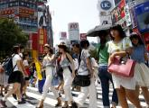 People cross a junction in front of advertising billboards in the Shibuya shopping district in Tokyo