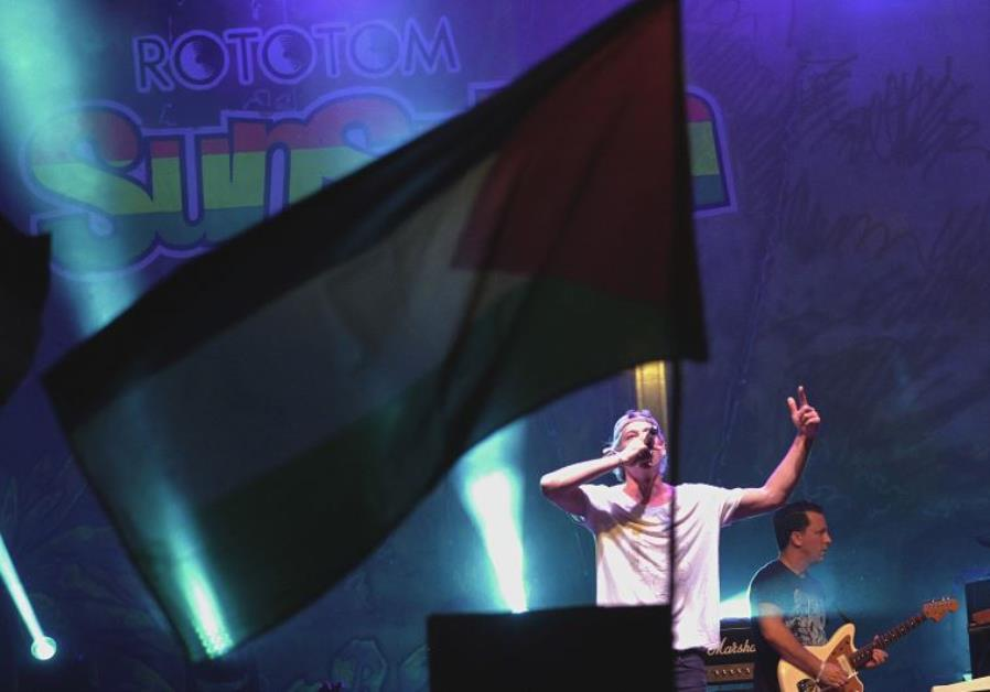 A Palestinian flag flies as Jewish musician Matisyahu performs on stage