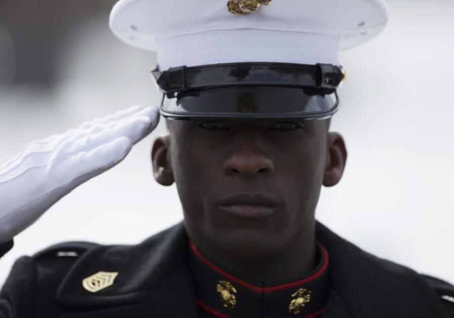 A Marine salutes the American flag during a wreath laying ceremony at the Marine Corps War Memorial