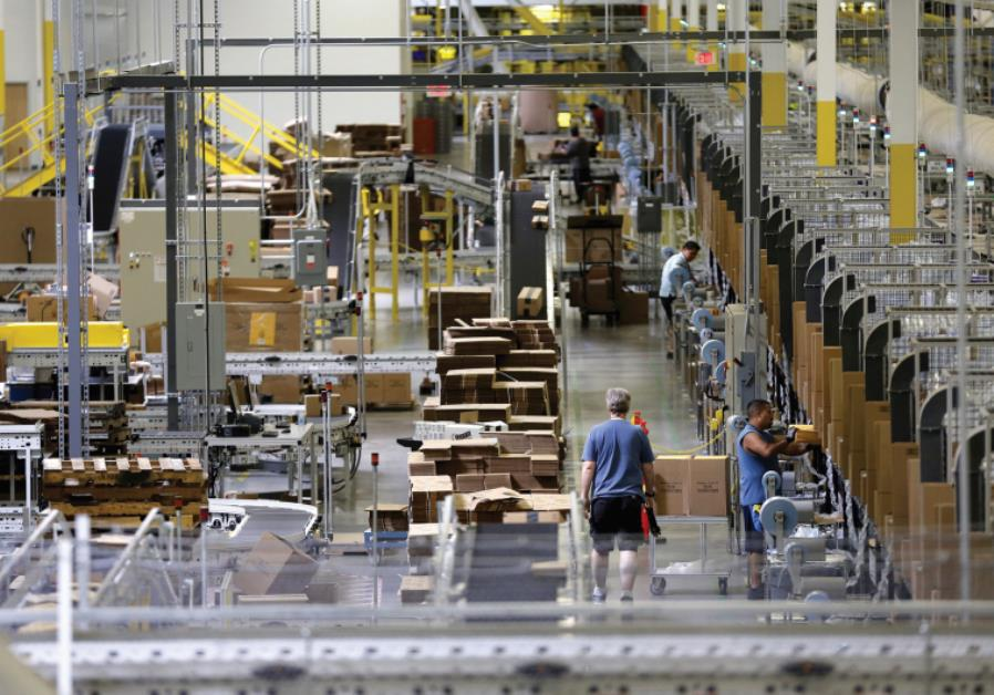 WORKERS SORT products at an Amazon Fulfillment Center in Tracy, California early this month