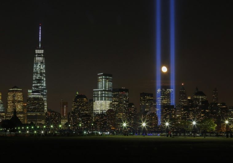 "The moon rises between the ""Tribute in Light"" illuminated next to One World Trade Center"