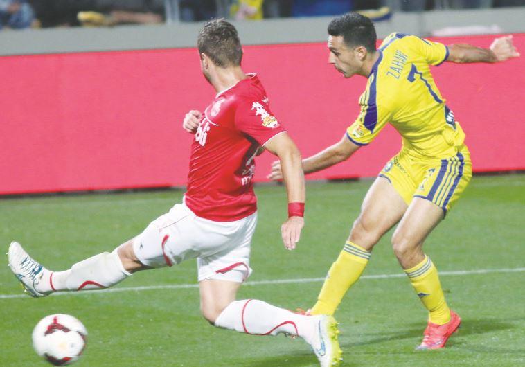 Maccabi Tel Aviv midfielder Eran Zahavi (right) kicking the ball during a match vs. Hap. Tel Aviv