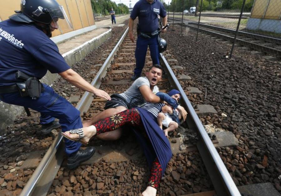 Hungarian policemen stand by the family of migrants as they wanted to run away
