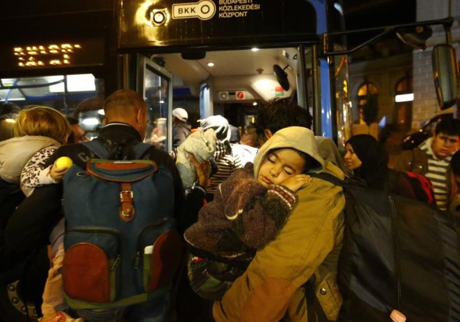 Migrants enter bus, which is supposed to leave to Austria and Germany, in Budapest, Hungary