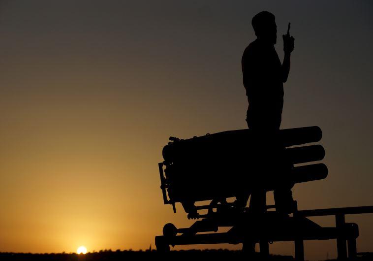 A Free Syrian Army fighter talks on a walkie-talkie near a rocket launcher in Daraa