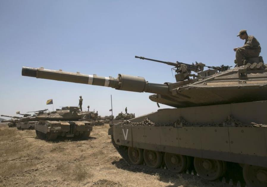 An Israeli soldier sits atop a tank during an exercise in the Golan Heights, near the ceasefire line