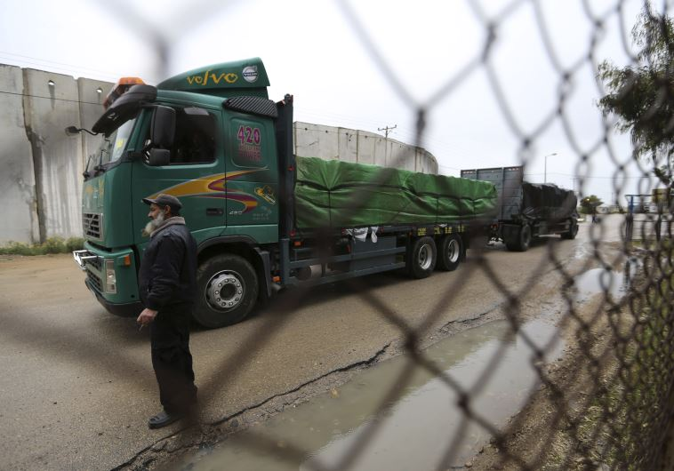 A Palestinian policeman stands guard as a truck loaded with fruits and vegetables waits to cross