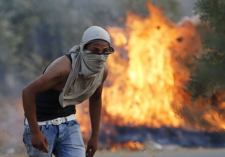 A Palestinian stone-thrower looks on as he stands in front of a fire during clashes with IDF troops