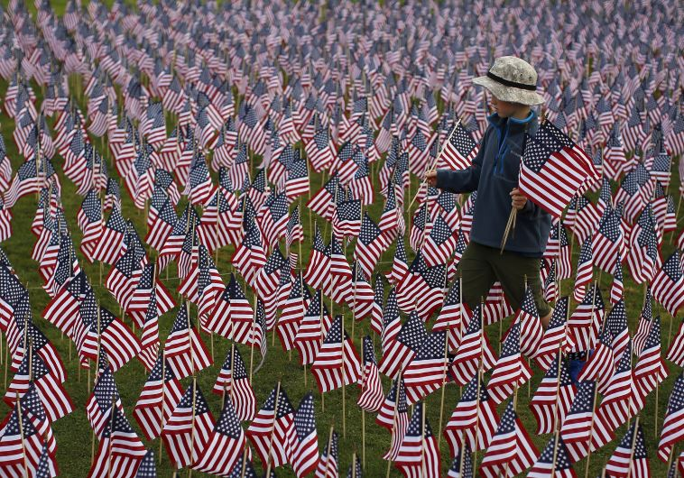Boy among some of the 3,000 flags placed in memory of lives lost in the September 11, 2001 attacks,