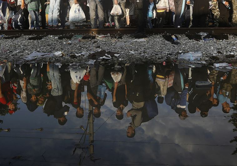 Syrian refugees are reflected in a puddle as they wait for their turn to enter Macedonia