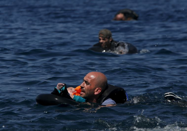 A Syrian refugee holding a baby in a lifetube swims towards the shore after their dinghy deflated