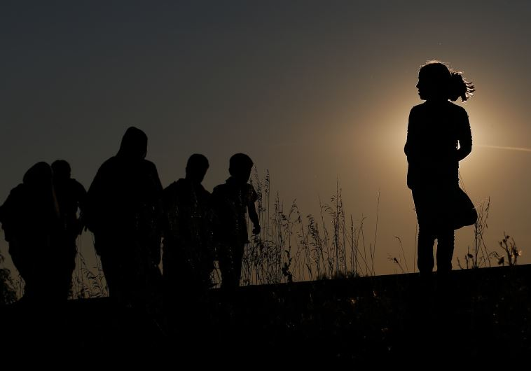 Migrants walk along rail tracks on sunset close to a migrant collection point in Roszke, Hungary