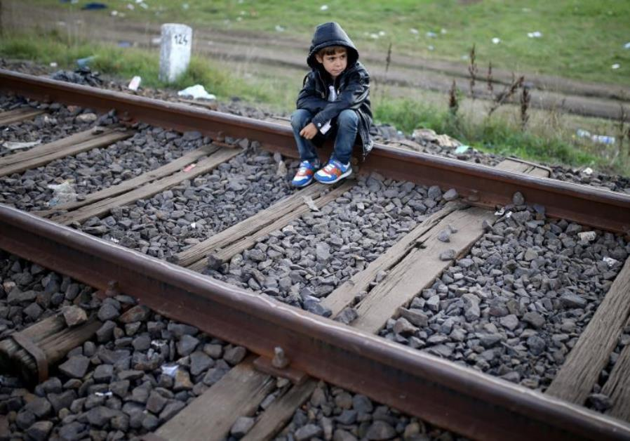 A migrant boy rests on railways after crossing into the country from Serbia