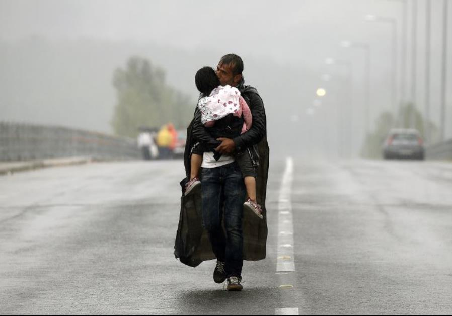 A Syrian refugee kisses his daughter as he walks through a rainstorm towards Macedonia