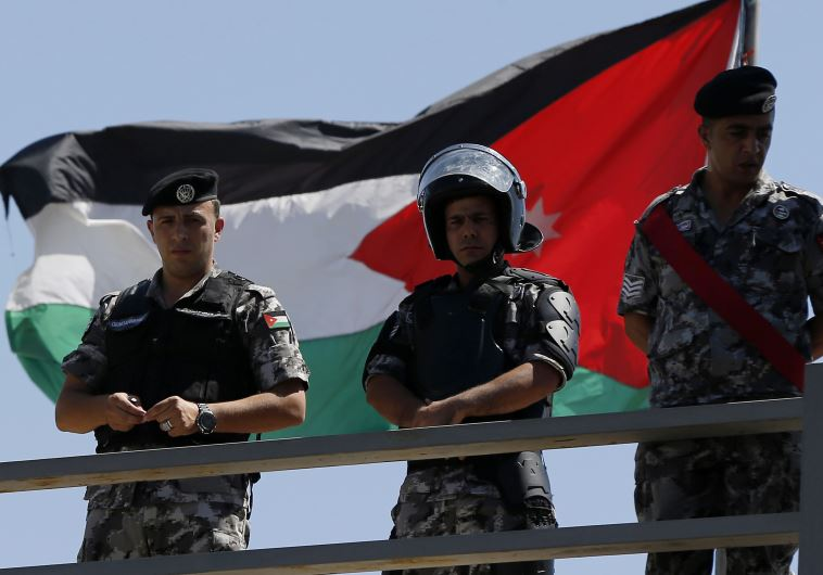 Jordanian riot police stand guard in front of a Jordanian flag as protesters hold a demonstration