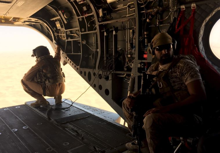 A soldier and an airman from the United Arab Emirates sit in a helicopter flying a small group of jo