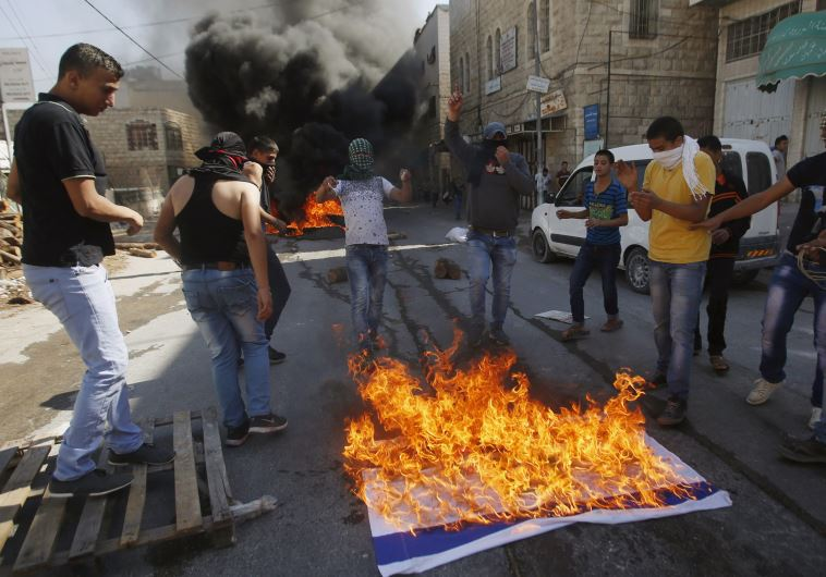 Palestinians in Hebron burn an Israeli flag while clashing with IDF troops