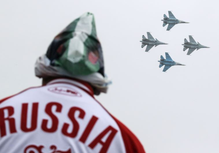 A spectator watches Sukhoi Su-30SM jet fighters of the Falcons of Russia acrobatic team