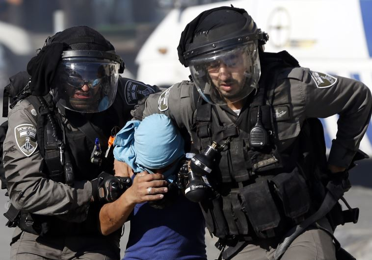Border Police arrest a Palestinian youth during clashes in the Palestinian refugee camp of Shuafat