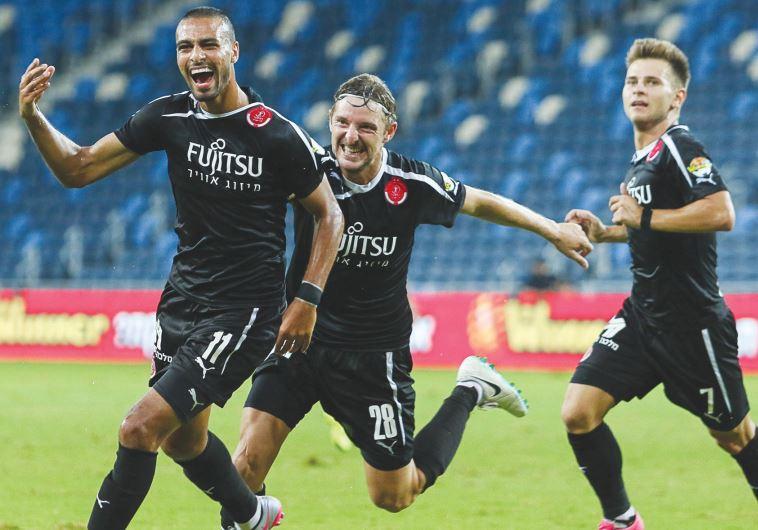 Hapoel Tel Aviv striker Ramzi Safuri (left) celebrates with teammates Liviu Antal (center)