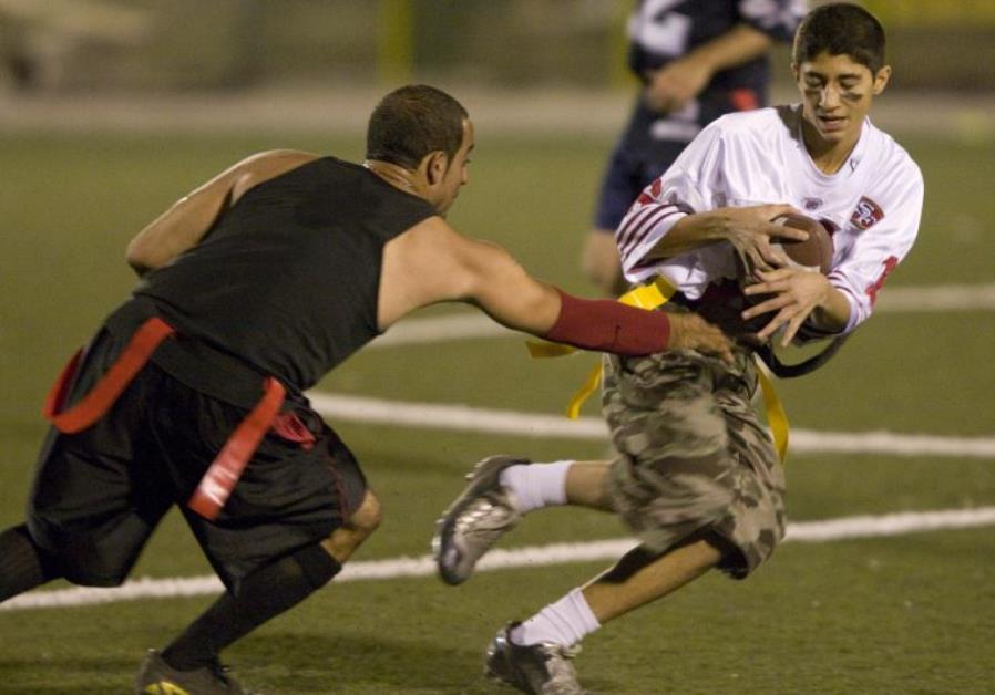 Amirhossein Sahiholnasab (R) tries to evade a tackle during the Tehran Titans flag football game