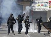 BORDER POLICEMEN fire tear gas at rock-throwers in the Shuafat refugee camp