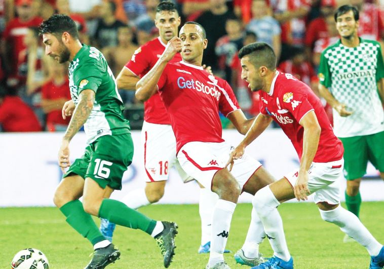 Maccabi Haifa striker Eliran Atar frustrated Hapoel Beersheba's Maharan Radi and Ben Biton