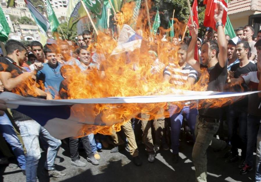Palestinian protesters burn an Israeli flag during a protest