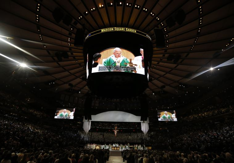 Pope Francis is shown on several large screens as he celebrates mass at Madison Square Garden