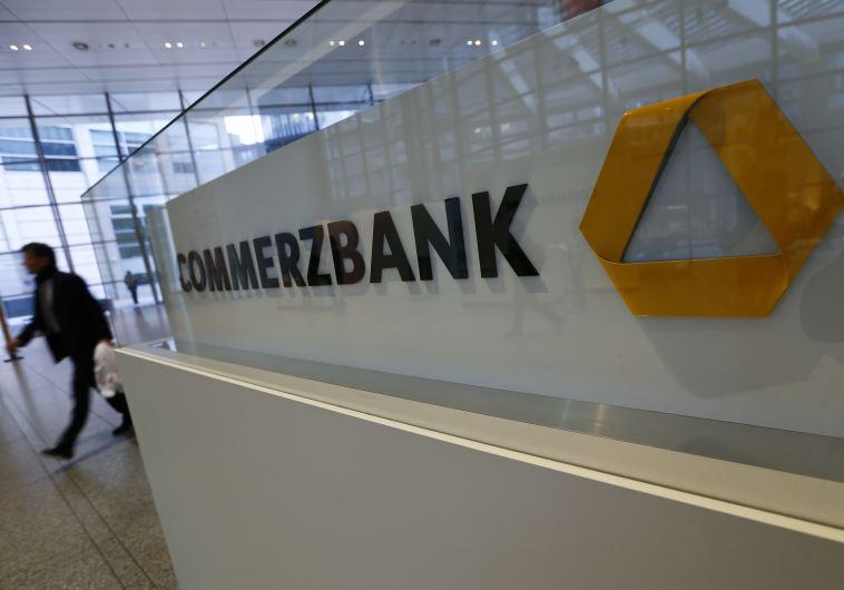 A man walks past a logo of Commerzbank